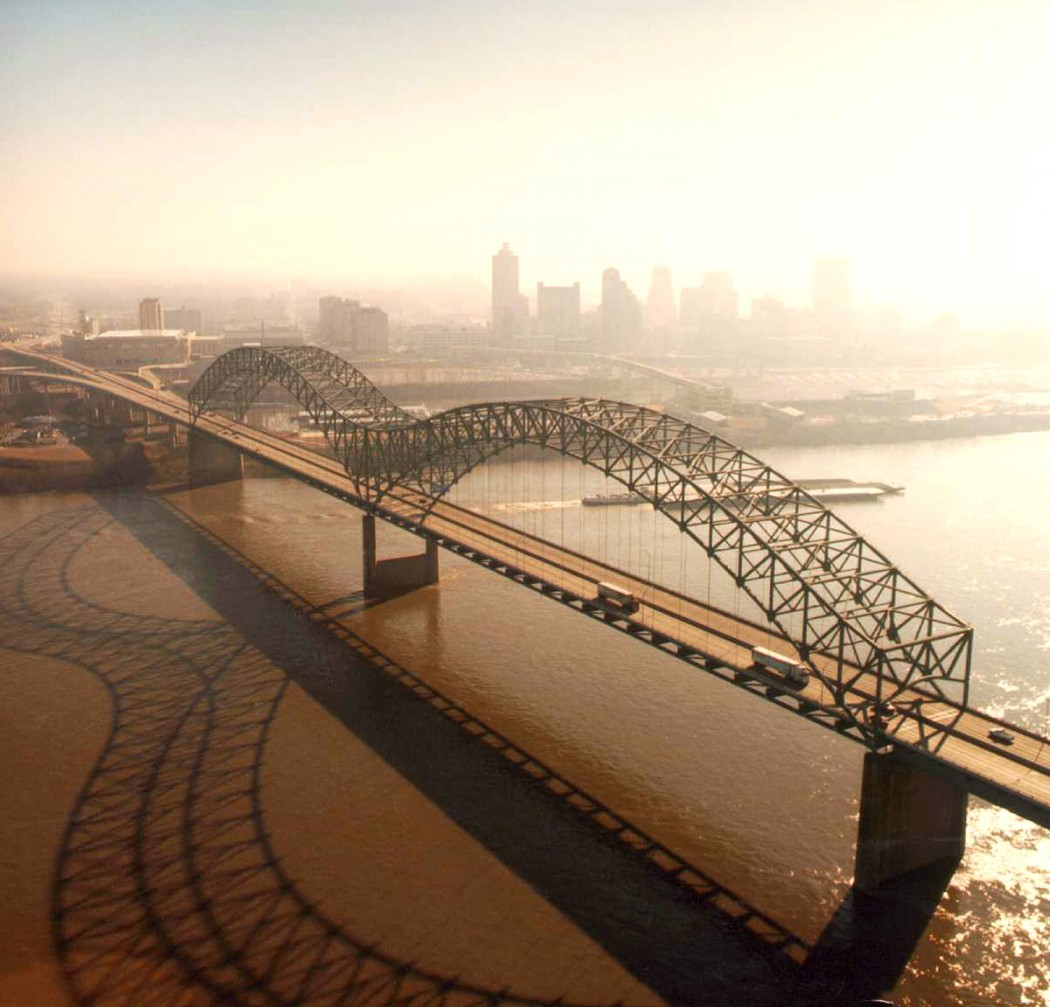 Aerial view of the Hernando de Soto Bridge across the Mississippi River between Memphis, Tennessee and West Memphis, Arkansas, USA. The bridge was opened in 1973 and carries six lanes of Interstate 40 across the river. View is from the Arkansas side to the east-southeast across the river to Memphis. Photographer Larry Donald, U.S. Army Corps of Engineers.