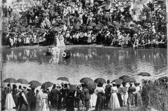 A large group of African-American spectators stands on the banks of Buffalo Bayou to witness a baptism, circa 1900. Courtesy of Special Collections, University of Houston Libraries.