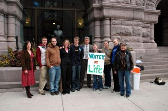 University of Minnesota students worked with Corporate Accountability International in 2008 to secure a ban on the sale of bottled water in Minneapolis City Hall. With the students in the photo are then-mayor R.T. Rybak (center) and current mayor Betsy Hodges (left), who was then on the Minneapolis City Council. Photo courtesy of Amber Collett.
