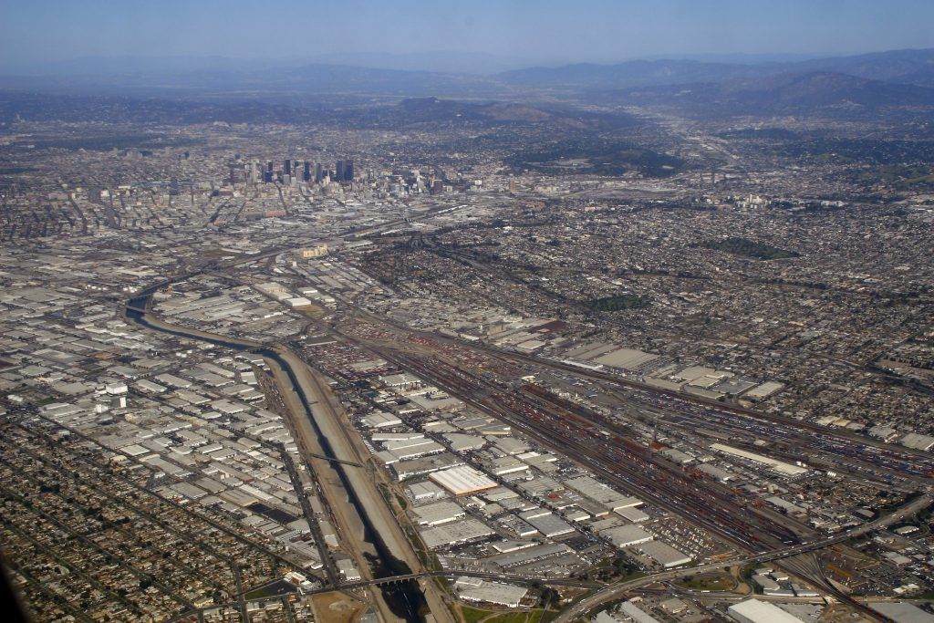 Aerial view of downtown Los Angeles (rear) and the Los Angeles River in industrial South Los Angeles (foreground).