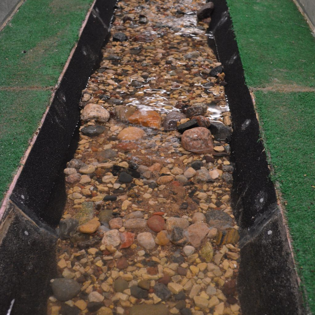 Experimental set up exploring sediment transport dynamics through culverts. Image courtesy of SAFL. Small stones appear in a long trough filled with water.