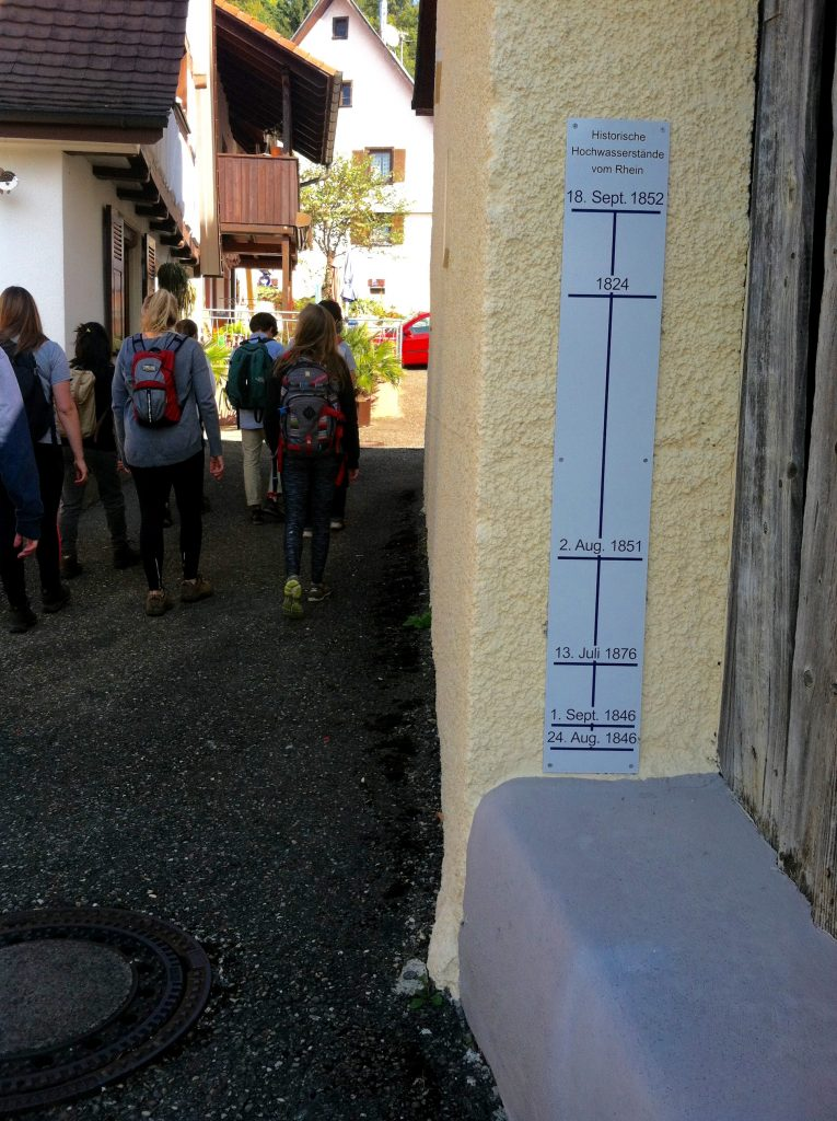 Students walk past a sign indicating historic flooding levels prior to channelization of the Rhine River in Istein, Germany. Image courtesy of Kristen Anderson.