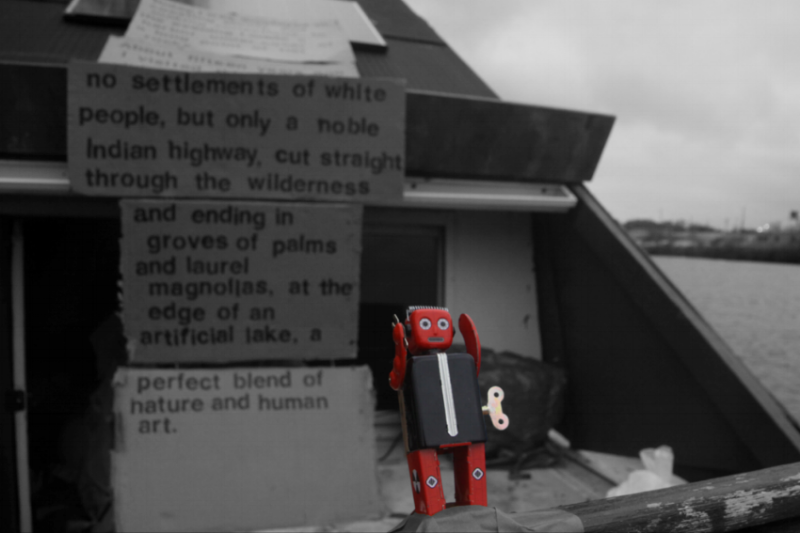 Bartram's Robot, 2016, Mason Rosenthal. Photographer Austin Bream. Behind a small toy robot on a boat there are signs reading 'no settlements of white people, but only a noble Indian highway, cut straight through the wilderness and ending in groves of palms and laurel magnolias, at the edge of an artificial lake, a perfect blend of nature and human art.'