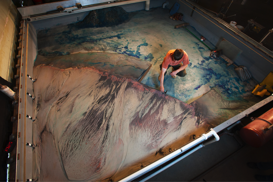 A SAFL student cuts into an experimental delta, revealing the stratigraphy of the deposits. Image courtesy of SAFL.