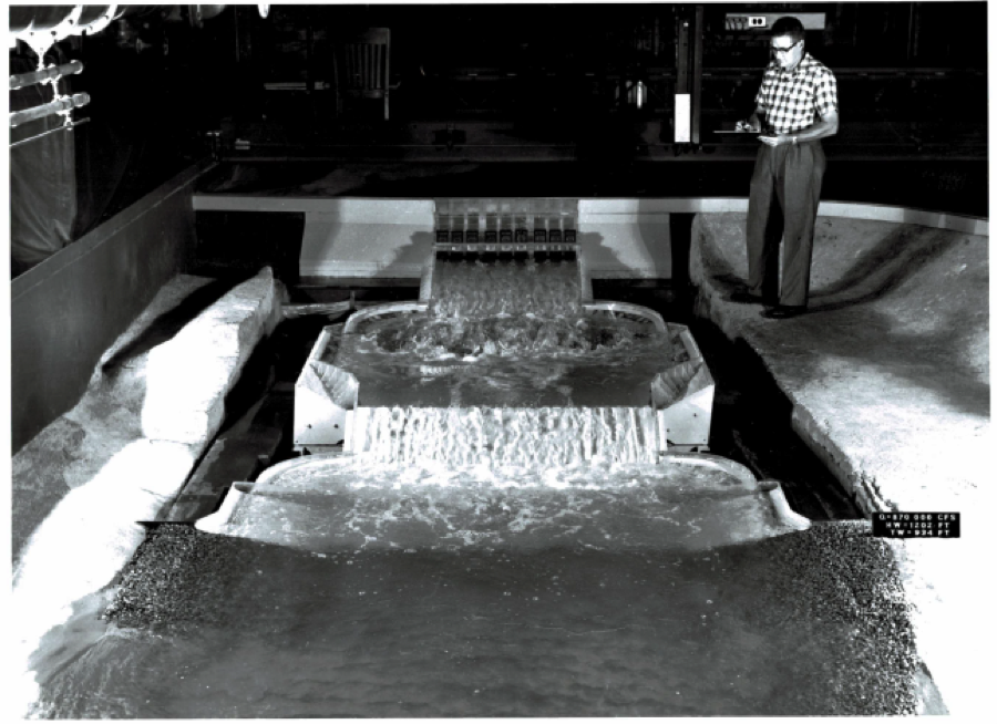 This model of the Mangla Dam shows the basin scheme where the upper basin had been enlarged from its original design to prevent erosion during high flow conditions. A man stands above the model and takes notes. Image courtesy of SAFL.