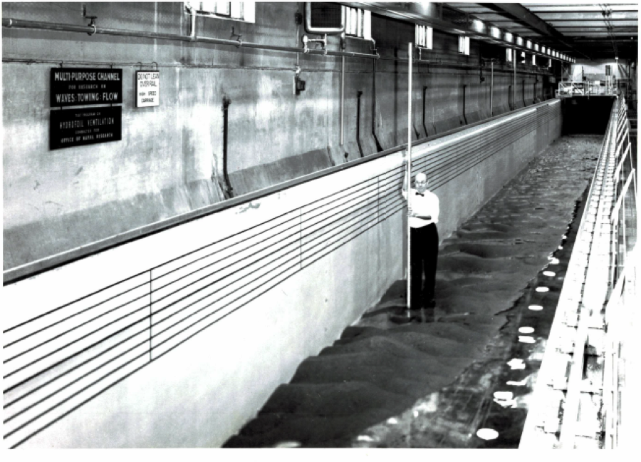 SAFL's Main Channel Flume, which extends the entire length of one floor and can run up to 300 cfs. A man stands in the flume, with a long tool which seems to be for raking.