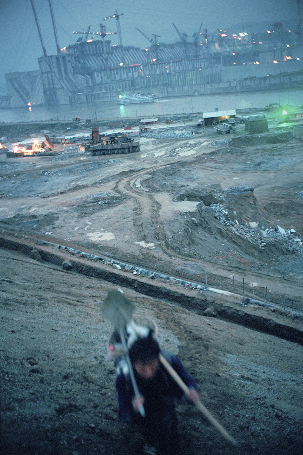A worker returning home after a day's work at the Three Gorges Dam construction site. In the distance, a three-storey boat is dwarfed by the gigantic 1.3 mile wide construction which has nearly blocked off the river. Although the final completion date for the dam is not until 2009, it has been operational since 1st June 2003.