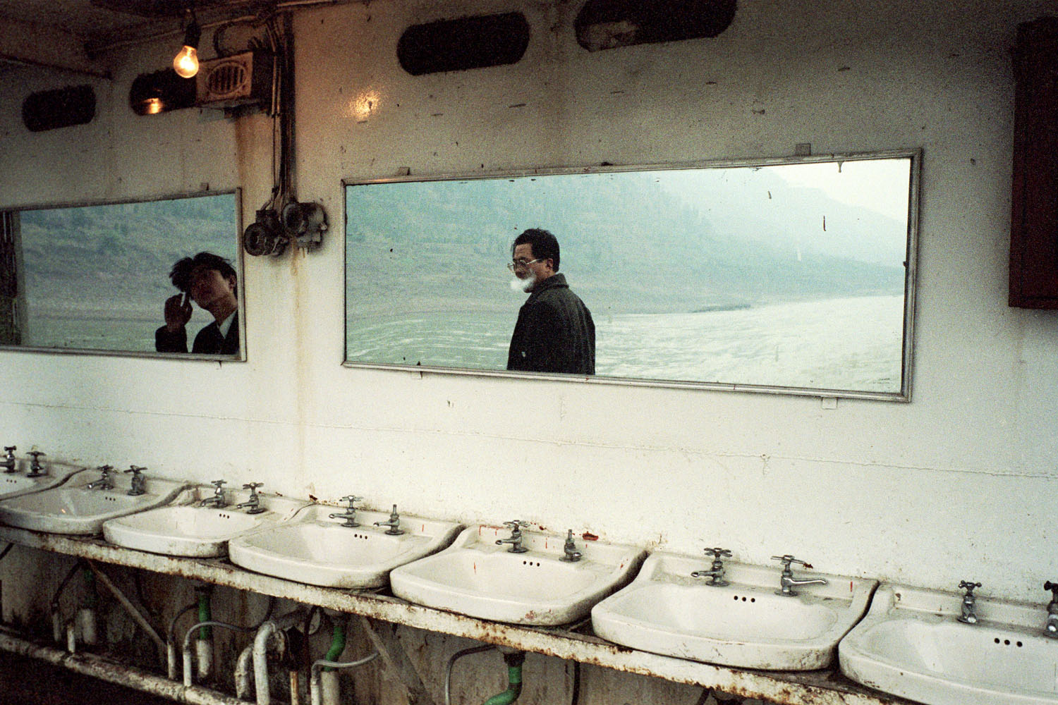 A row of sinks on an old passenger boat on the waters of the Yangtze River. Two individuals are visible in the mirrors above the sinks.