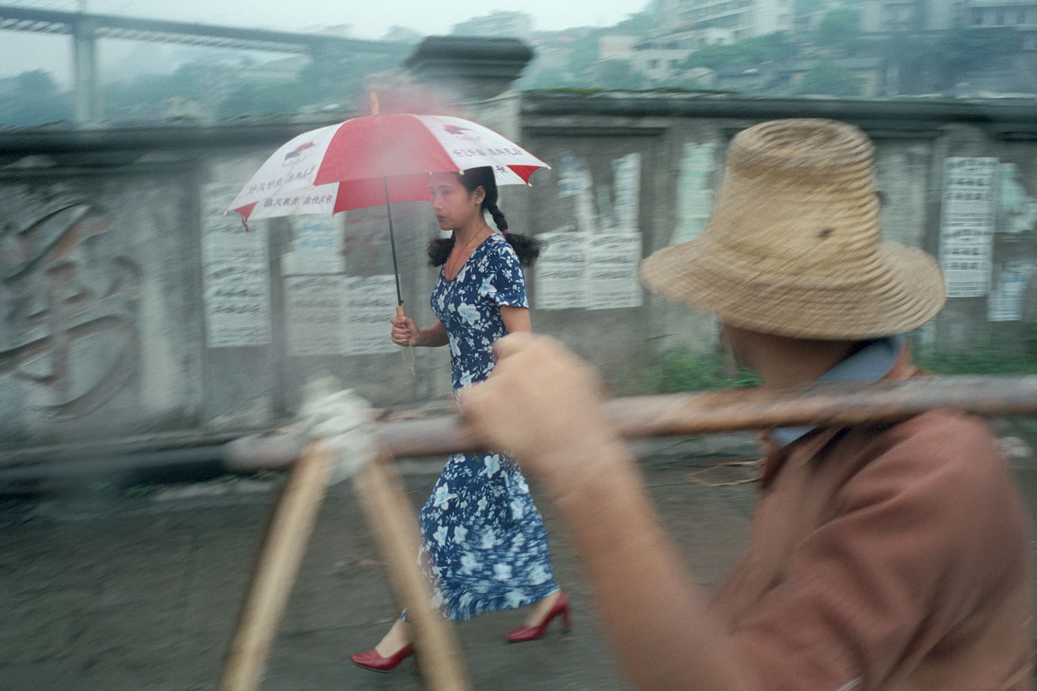 The last vestiges of normal life in a town that has virtually been destroyed. A woman in a bright blue dress and red shoes walks with an umbrella along the sidewalk. The mass exodus of its population has turned the old section of the city into a ghost town. Wanzhou bridge once the defining landmark of the city is now weeks away from being dynamited.
