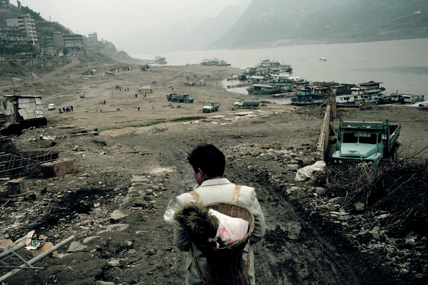 Migrant worker heading to the local docks after the recent demolition of the town. Zigui, China. 2000.