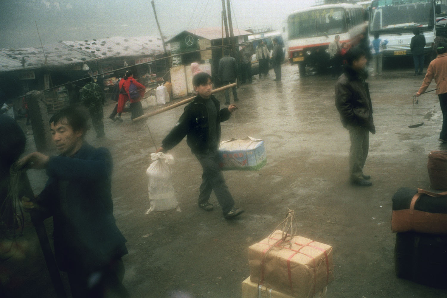 Laborers carrying belongings with a traditional shoulder pole at the bus station for inhabitants relocating to the new town. Yunyang, China. 2000.
