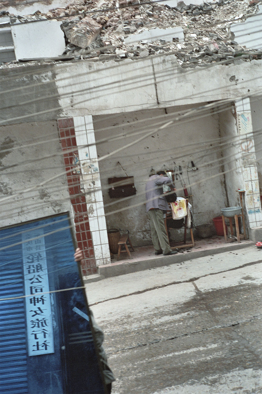 One of the last remaining inhabitants, a barber works in a demolished high-rise building where only the ground floor remains intact. In the foreground, a laborer walks past carrying a mirror salvaged from a building soon to be demolished. Wushan, China. 2002.