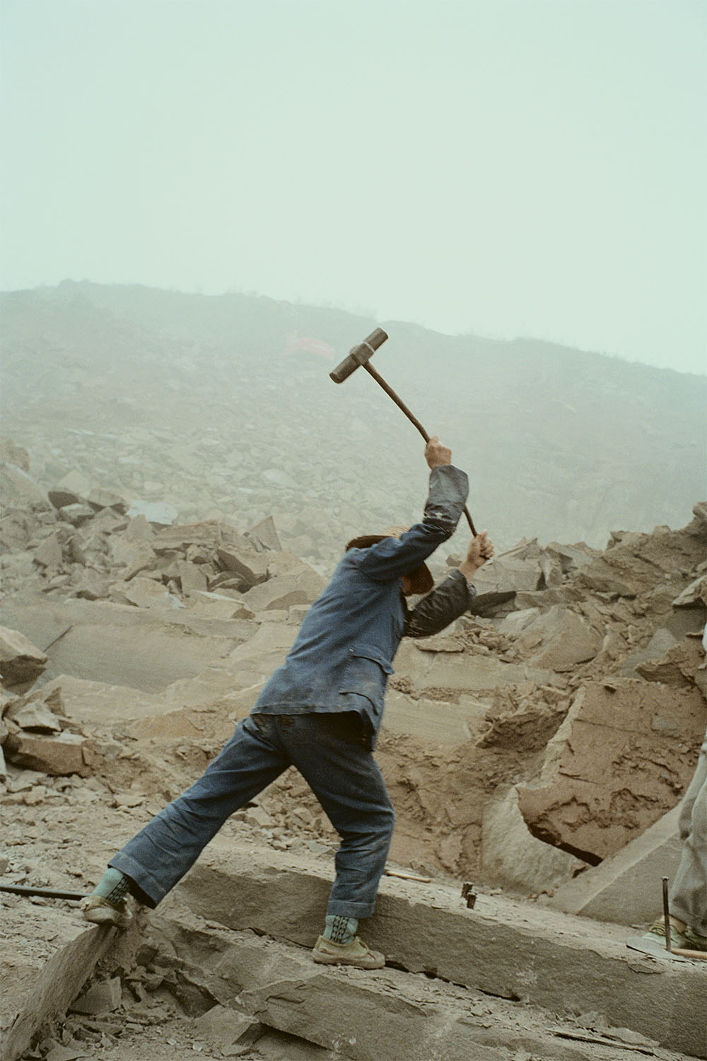 Migrant worker at a construction site in the new town. The town is built higher up the mountains and will replace the old town that will eventually be submerged upon the completion of the Three Gorges Dam. Yunyang, China. 2000.