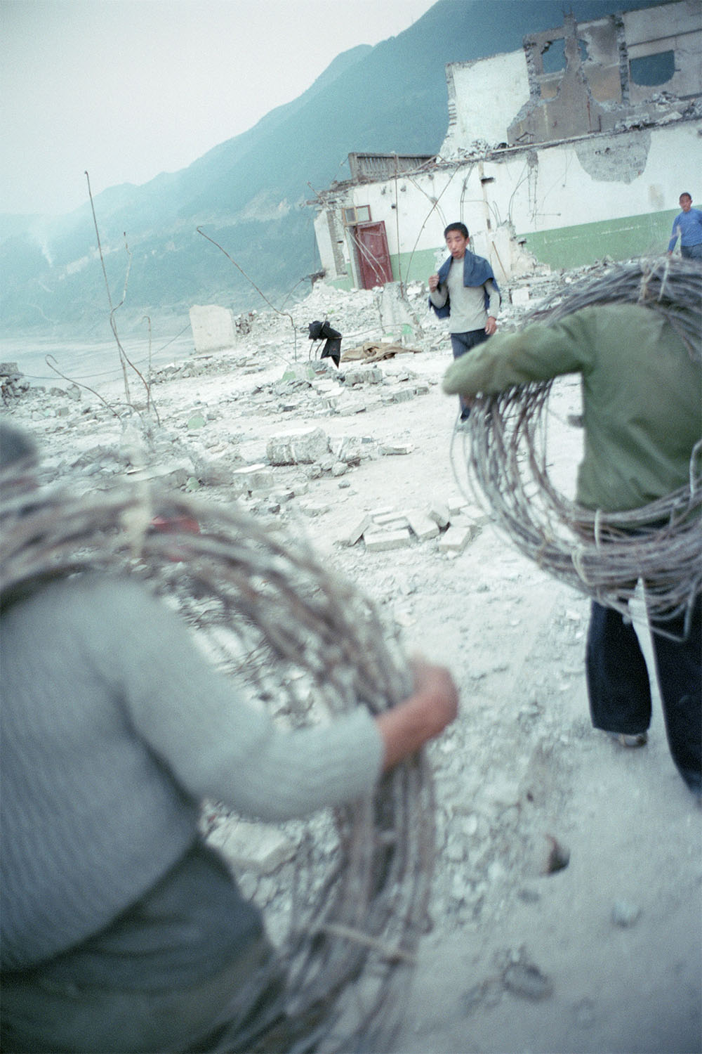 Migrant workers dismantling a recently vacated building. The workers supplement their poor income by selling scrap metal and bricks salvaged from demolition sites. Badong, China. 2002.