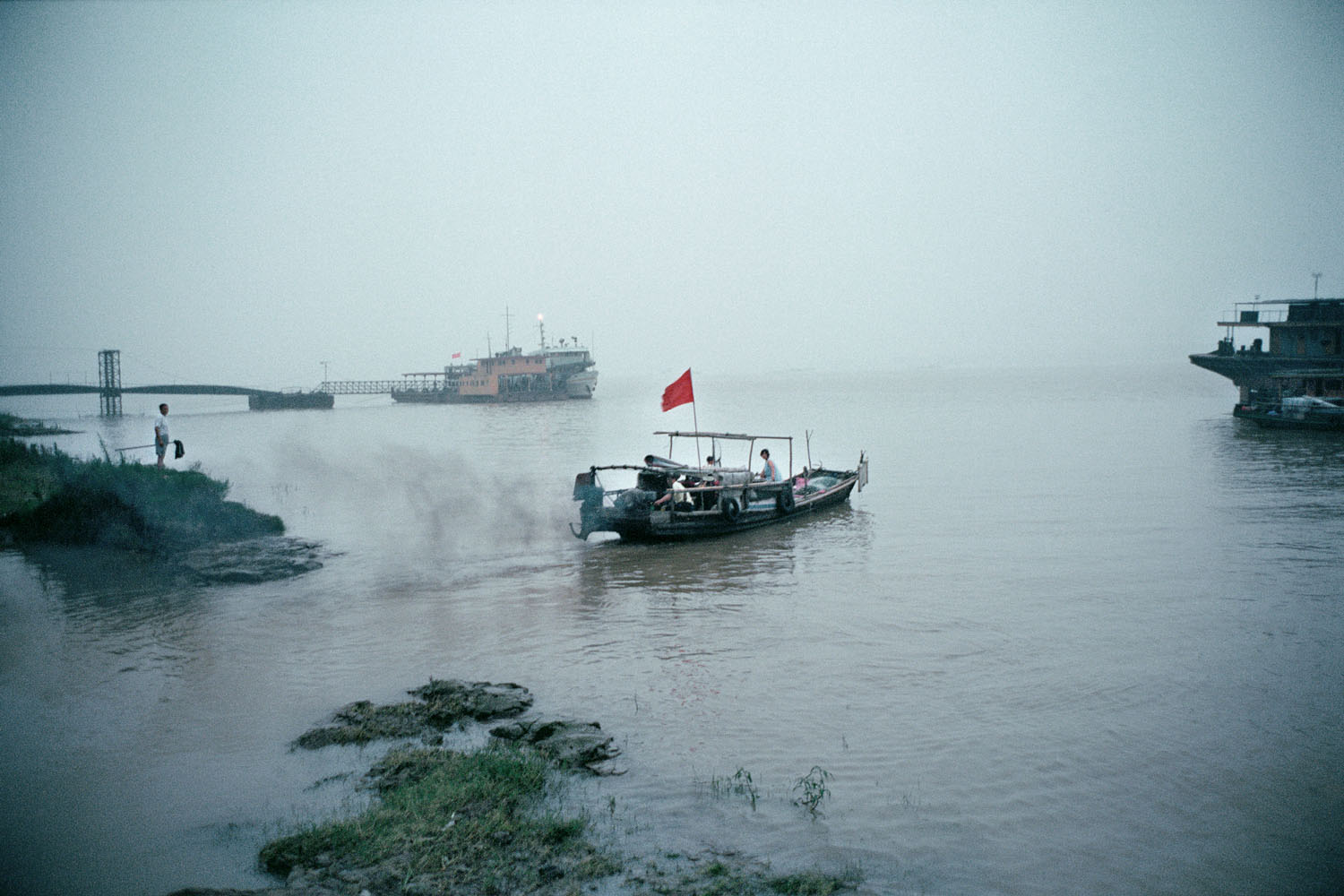Daily life on the Yangtze River. A boat with a red flag sails away into the distance on a foggy day. China. 2001.