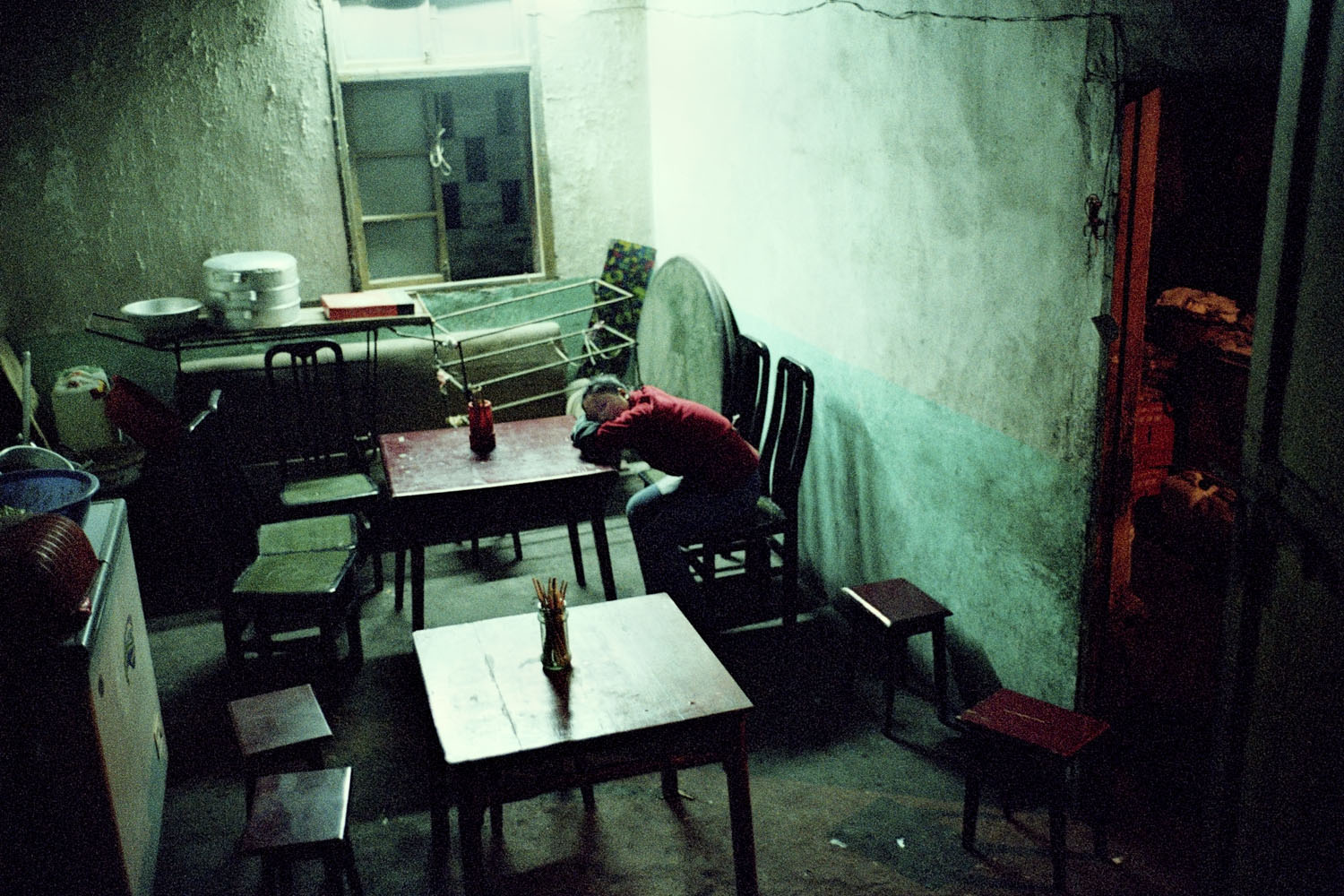 Last inhabitants. A woman sits alone at a table with many chairs surrounding it. As the last inhabitants move out, business activity of these old towns ground to an inevitable halt. Badong, China. 2002.