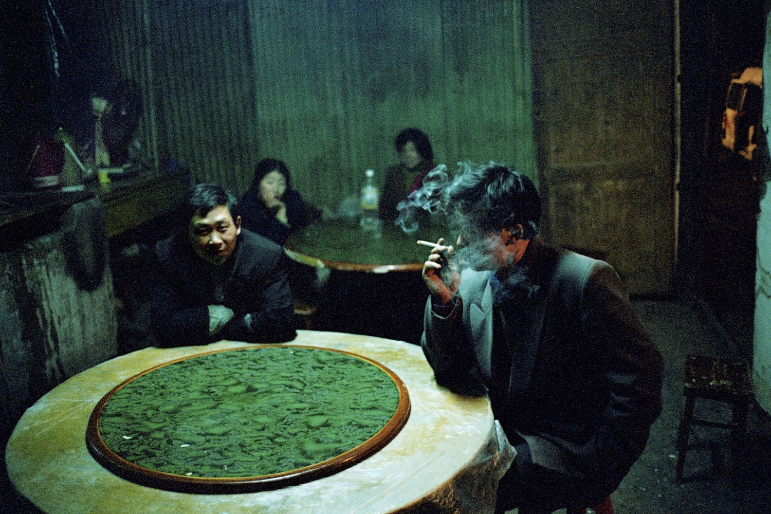 Locals sitting in a local eatery. They have not ordered food, but are instead using the space to rest, whilst outside buildings are being demolished. As the last inhabitants of the town move out, the business activity of these old towns ground to an inevitable halt. Badong, China.