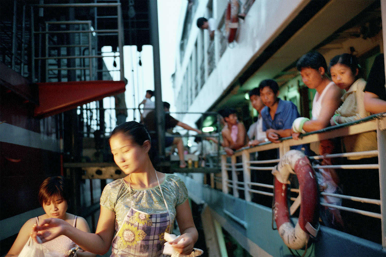 A street vendor selling food to passengers on a boat. Yichang, China. 2001.