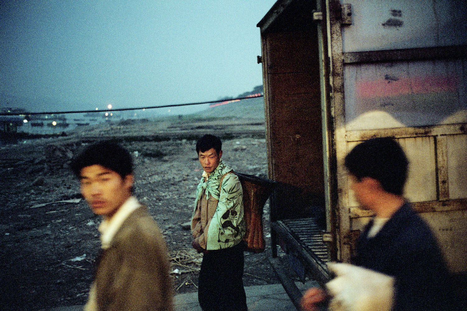 Migrant workers stand in front of a truck at night. Yichang, China. July 2001.