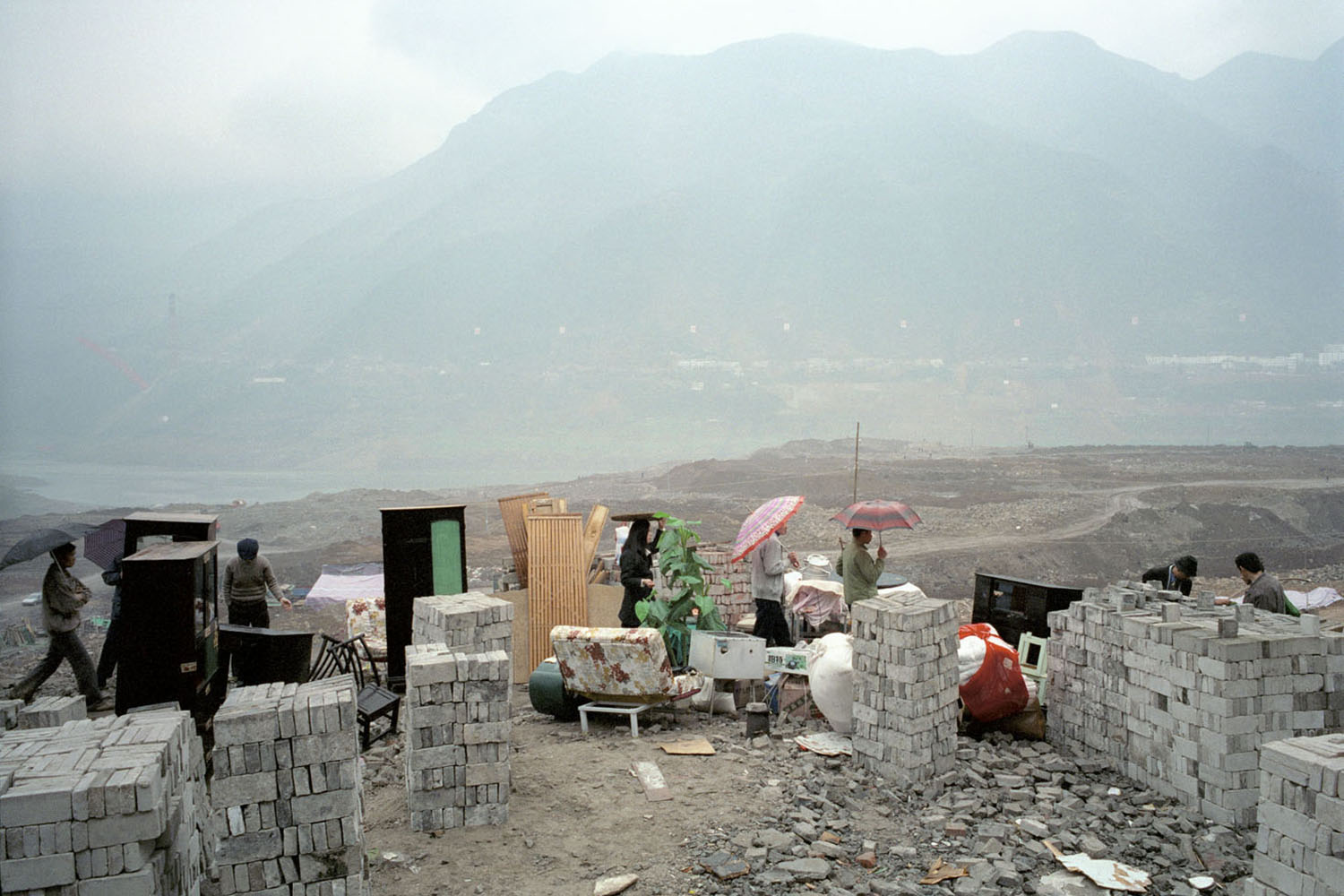 The last remaining family moves home. In the background is a levelled construction site, this used to be the site of the old city. Wushan, China. 2003.