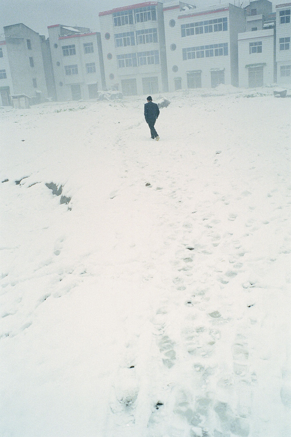 A lone man in a suit walks through the snow towards a row of buildings.