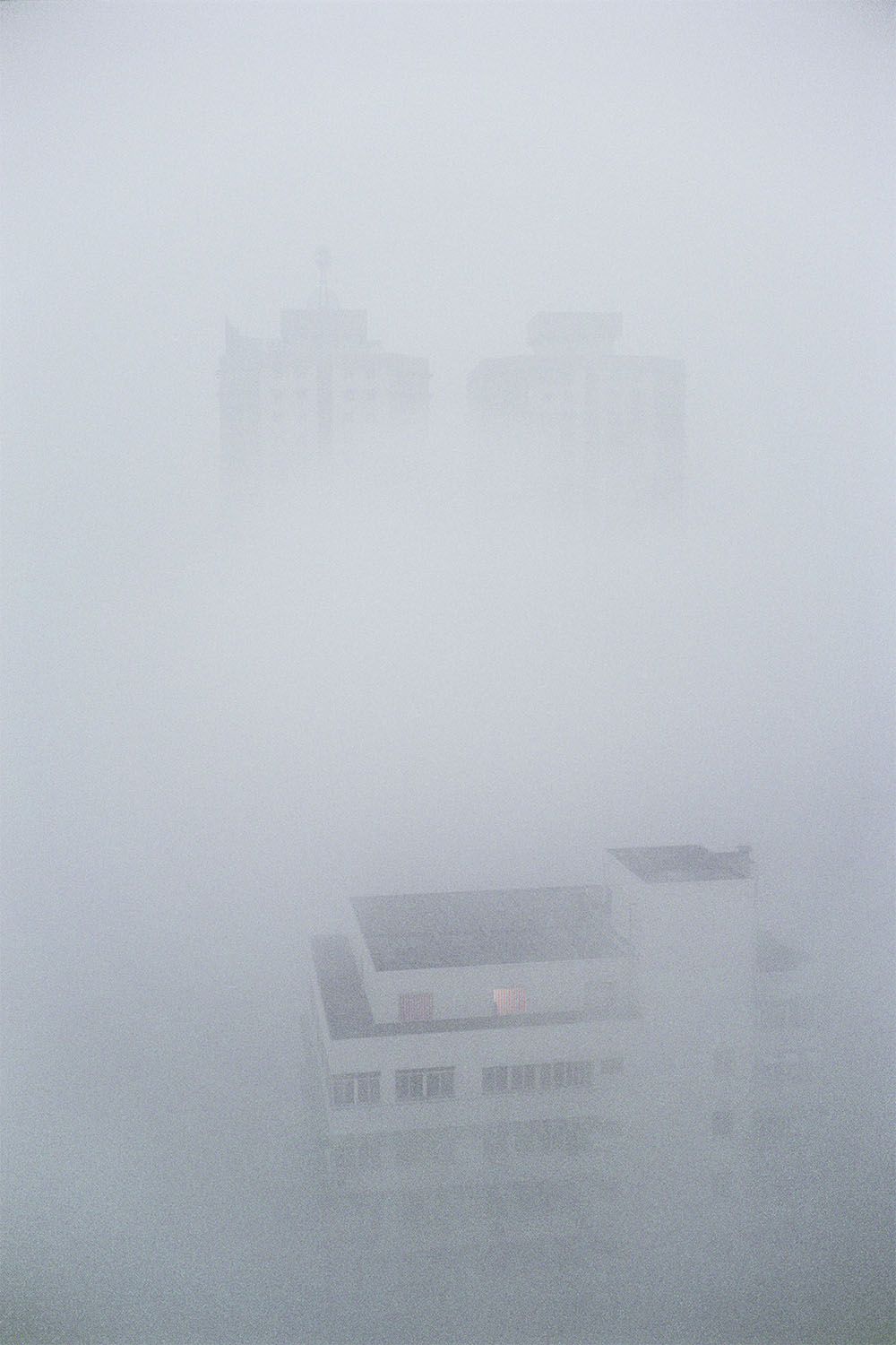 New construction higher up on the hills of the Yangtze River. The buildings are surrounded by a heavy fog. Chongqing, China. 2000.