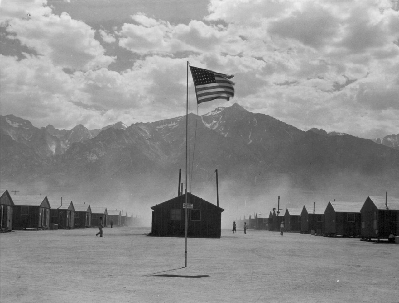 cene of barrack homes at this War Relocation Authority Center for evacuees of Japanese ancestry at Manzanar. A hot windstorm brings dust from the surrounding desert. Photographer Dorothea Lange, 1942.