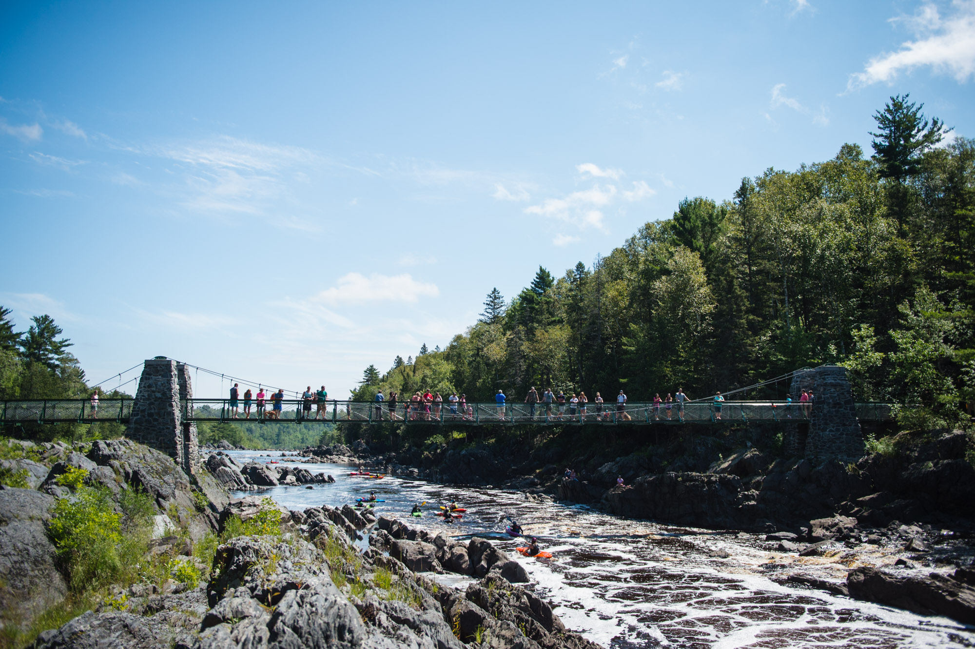Visitors to Jay Cooke State Park watch kayakers from the iconic Swinging Bridge. Image courtesy of Alex Messenger Photography.