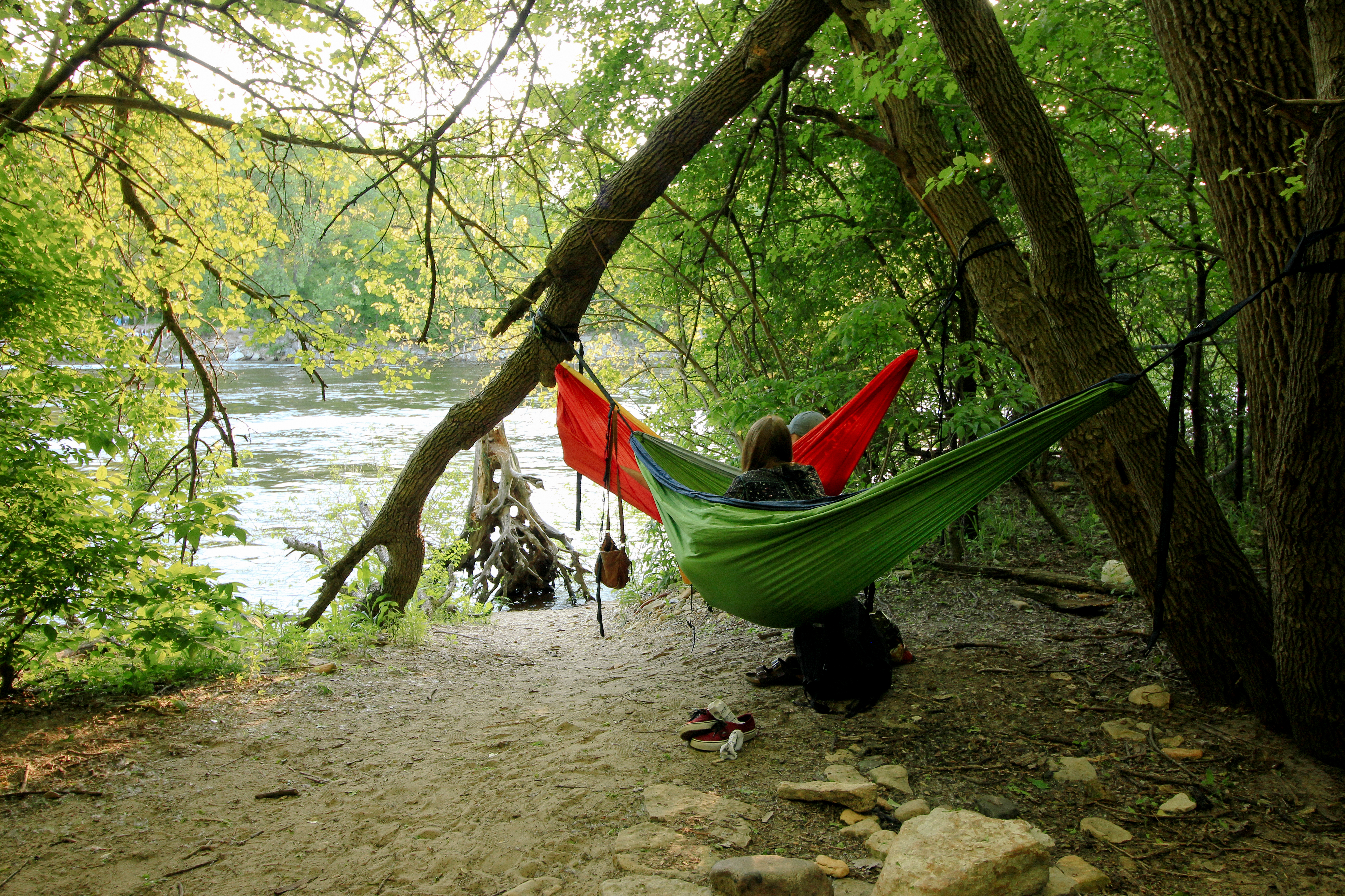 Hidden Falls Regional Park. Two people sit in individual hammocks in a shady area near a river. Photographer Erin D. Carter.