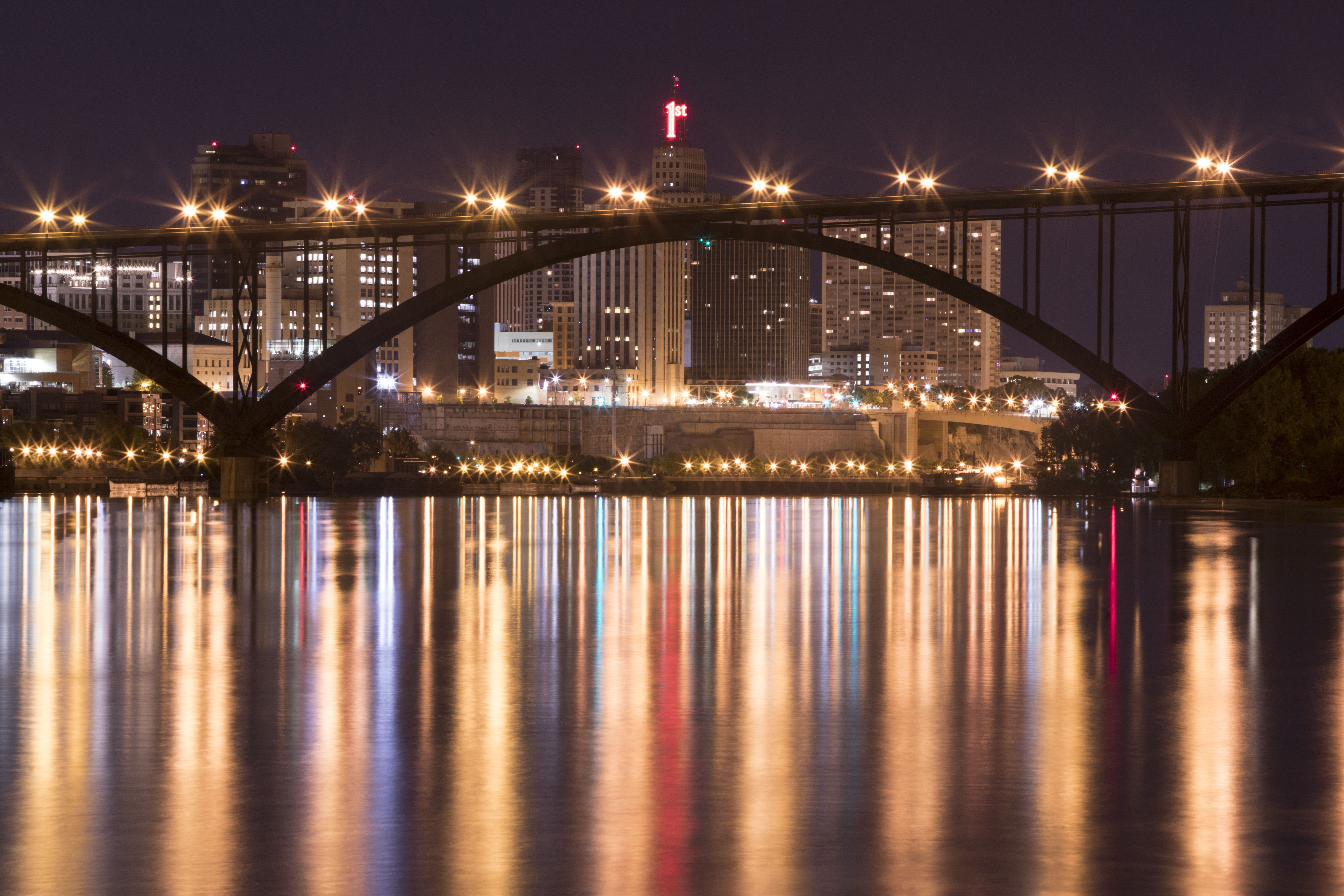 Lilydale to St. Paul. Lights from downtown St. Paul at night are reflected on the Mississippi river. Photographer Chris Juhn.