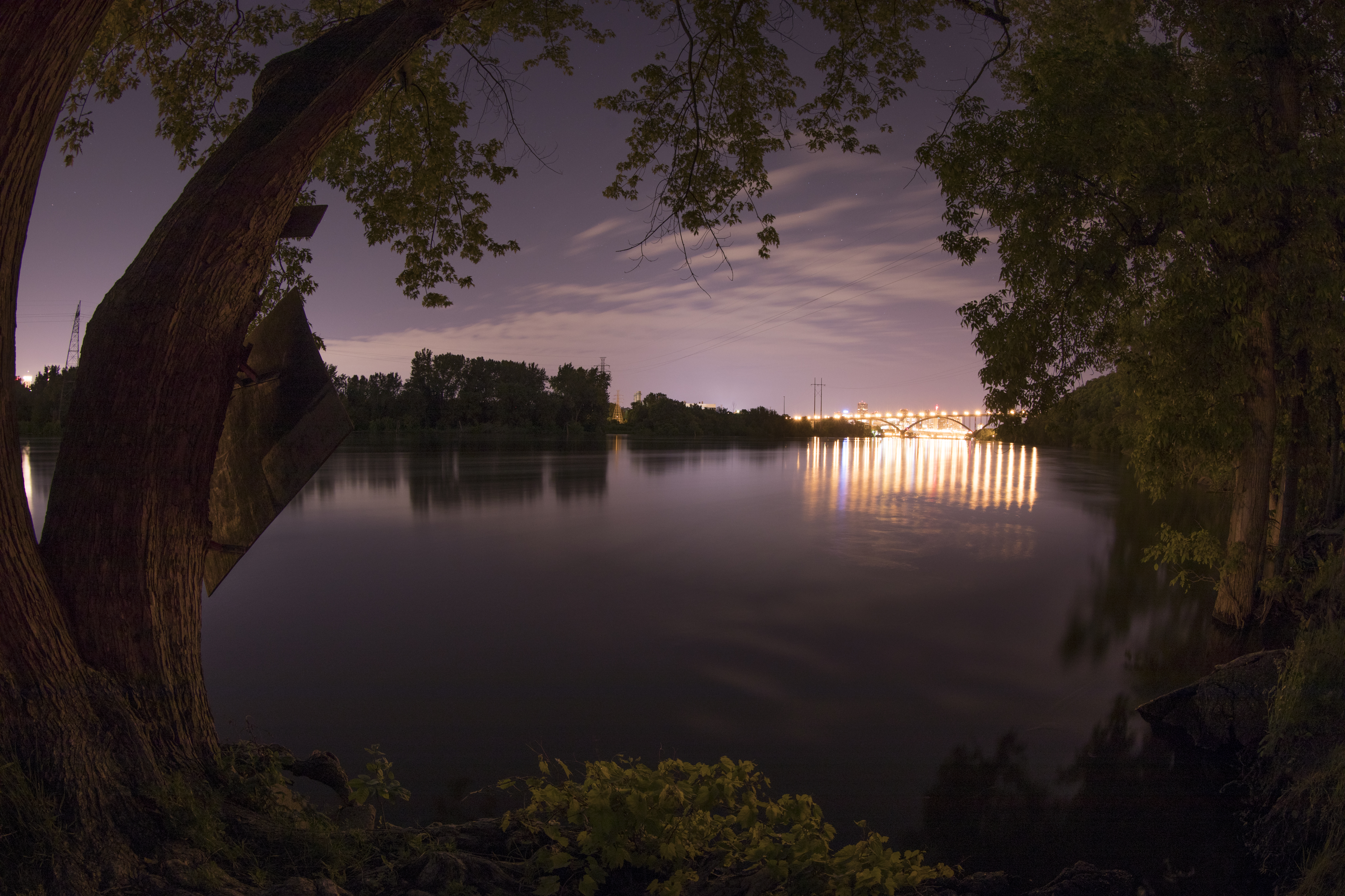 Lilydale to St. Paul. A fisheye shot of the Mississippi river at night, with Downtown St. Paul visible in the distance. Photographer Chris Juhn.