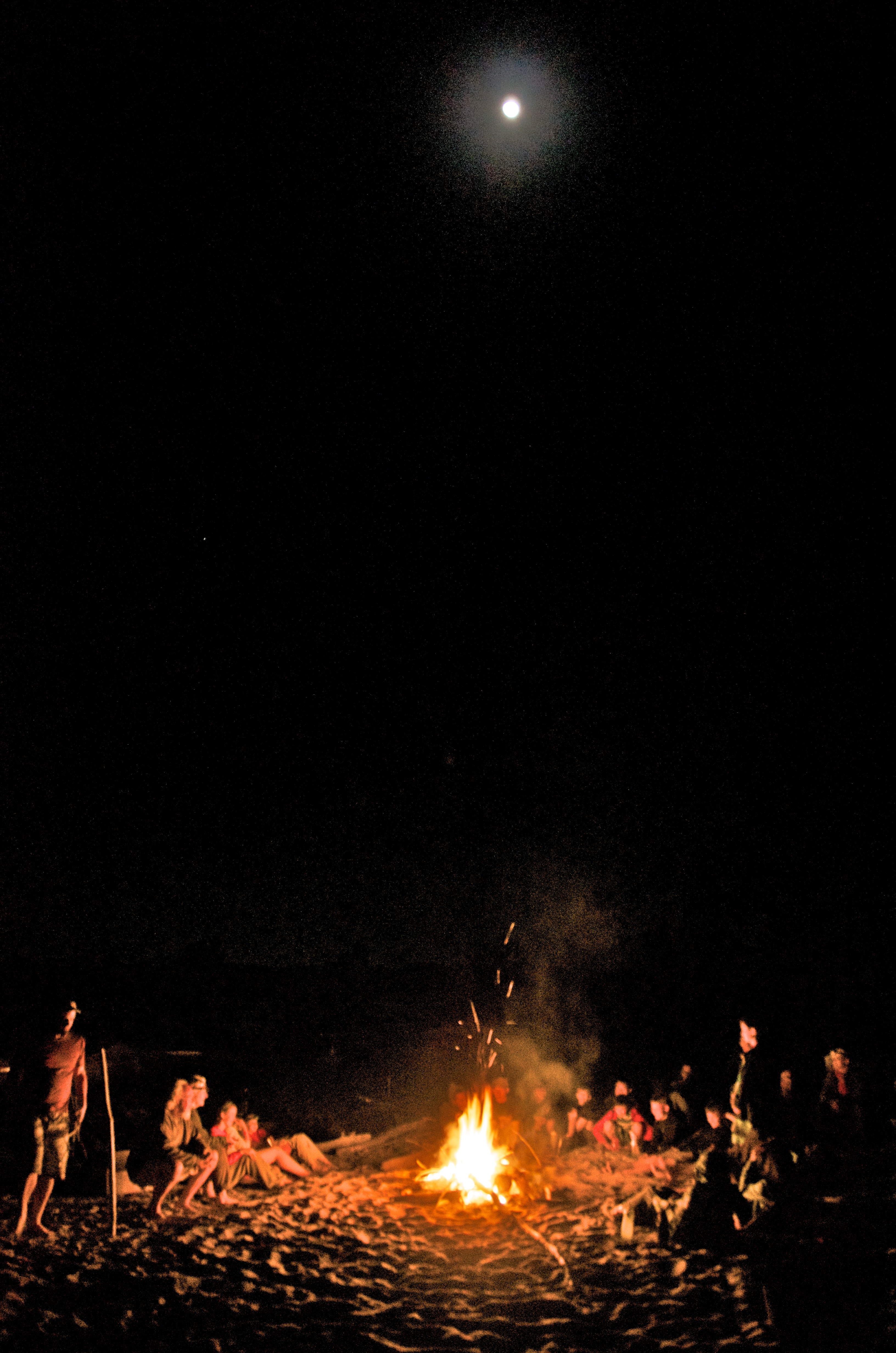 Learning on the river takes many forms. A group sit around a campfire at night, and the moon shines brightly above them. Image courtesy of John Ruskey.