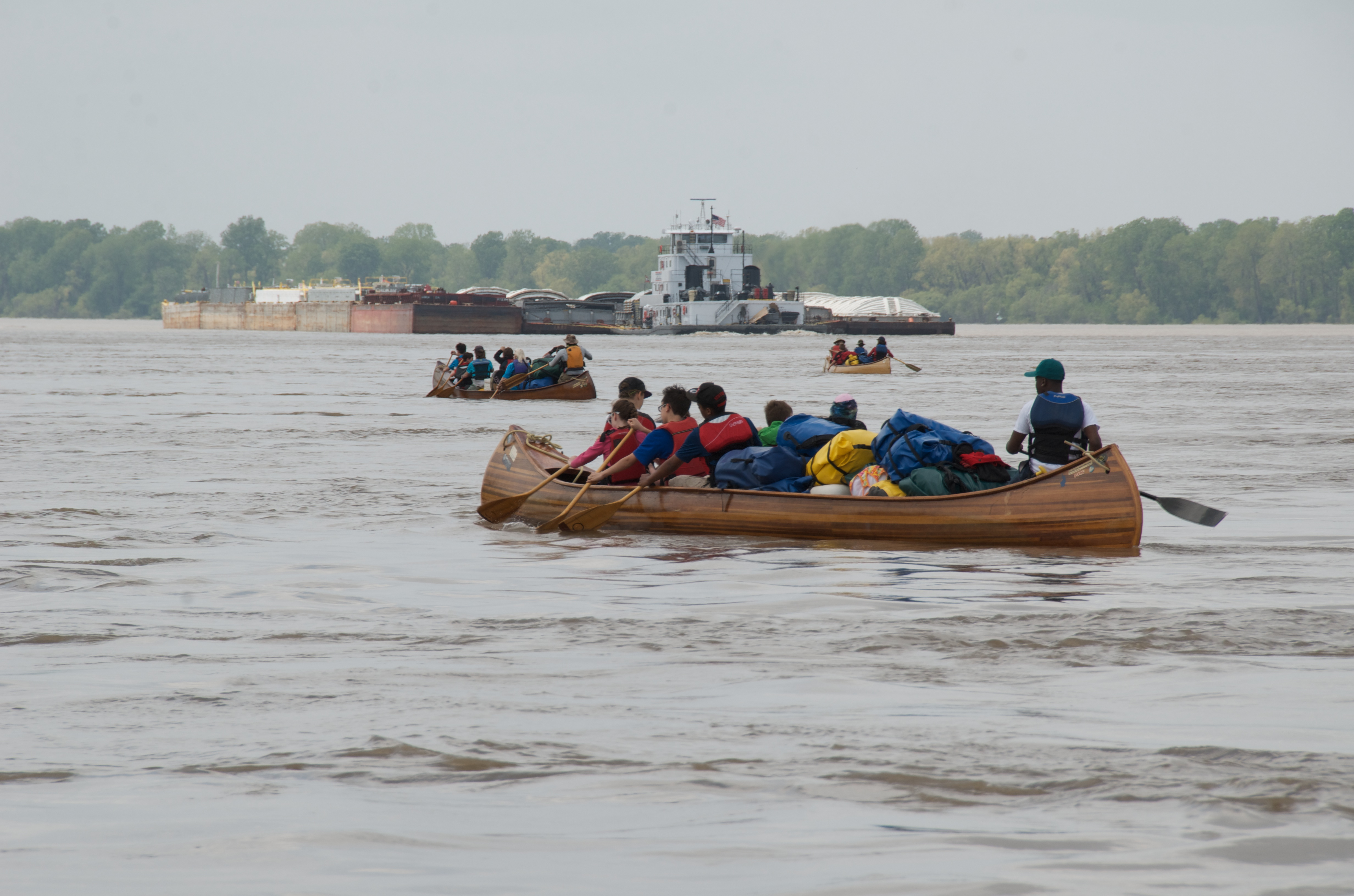 Sharing the waters. Three canoes appear on the river, with a much larger barge appearing in the distance.