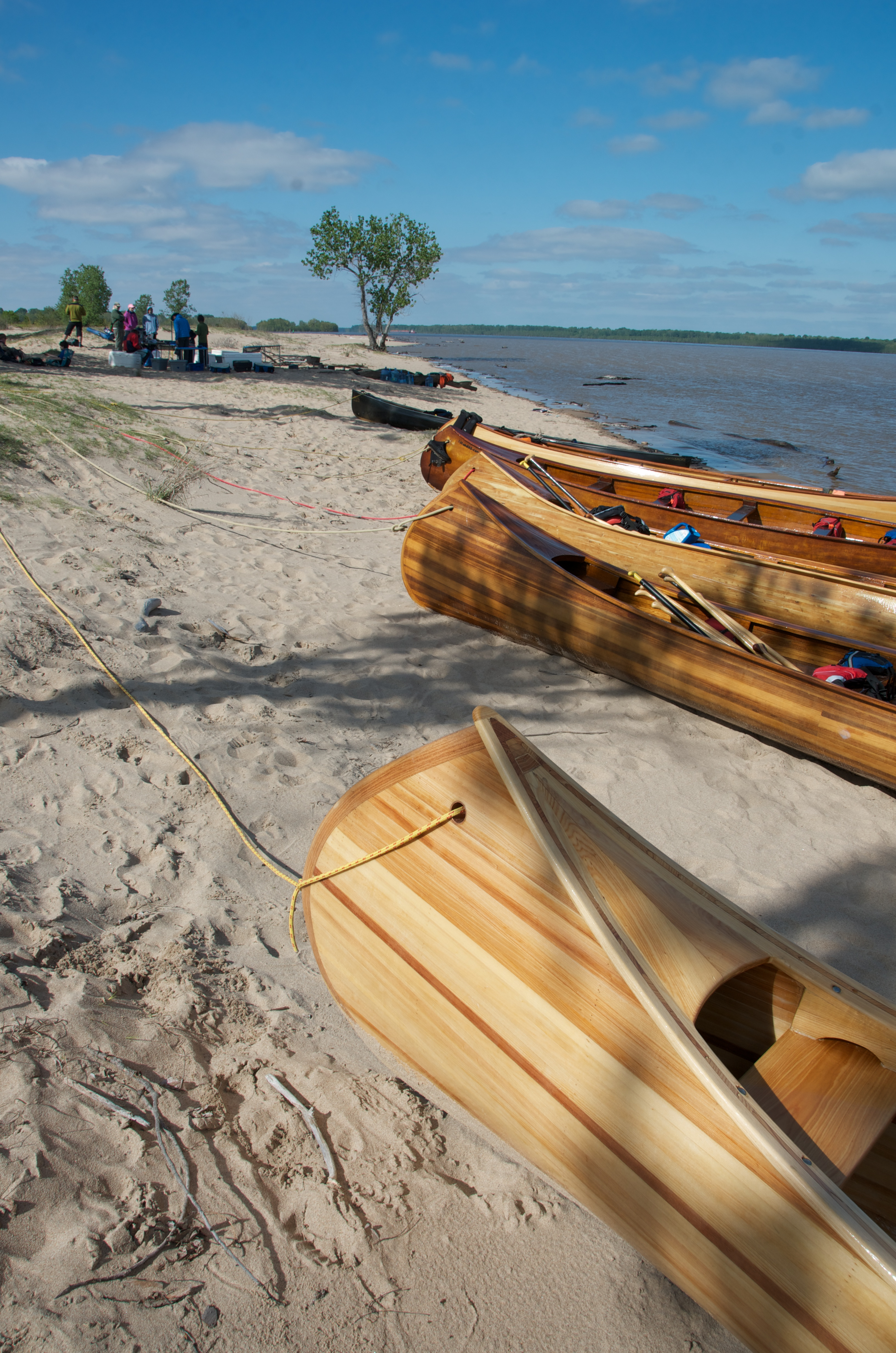 Public spaces on the river are critical. Many canoes sit unoccupied on a sandy beach. Image courtesy of John Ruskey.