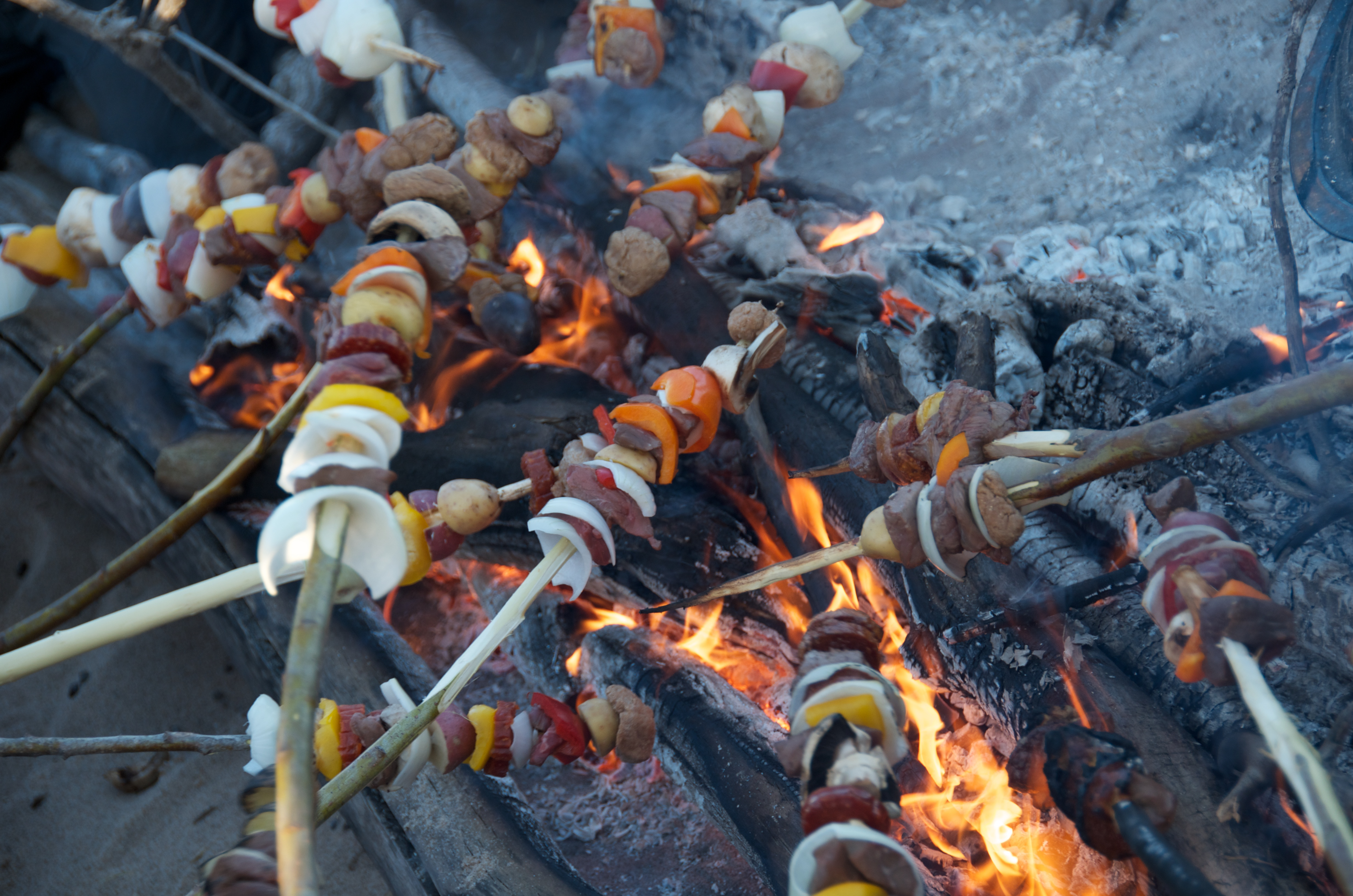 Dinner time. Different skewers are held over a campfire. The skewers have mushrooms, onions, peppers, beef, and potatoes on them.