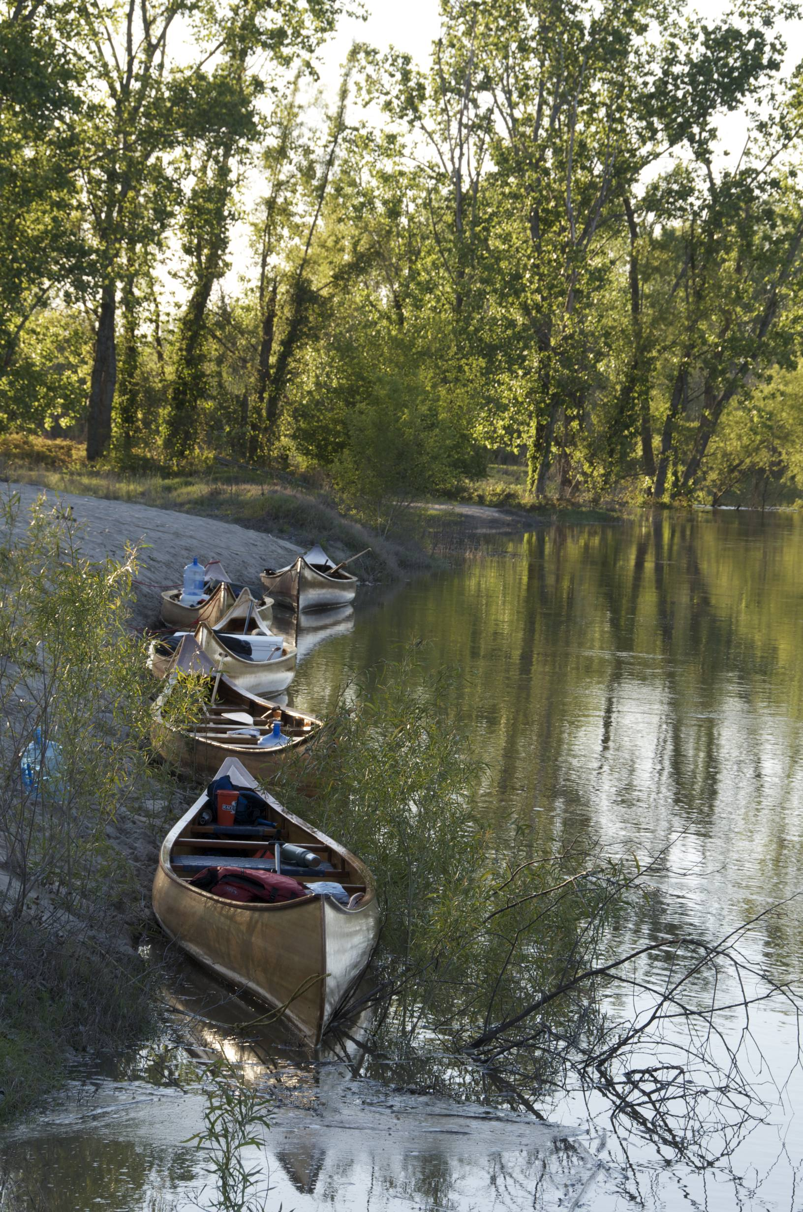 Getting people on the river. Five empty canoes sit at the shore. Image courtesy of John Ruskey.