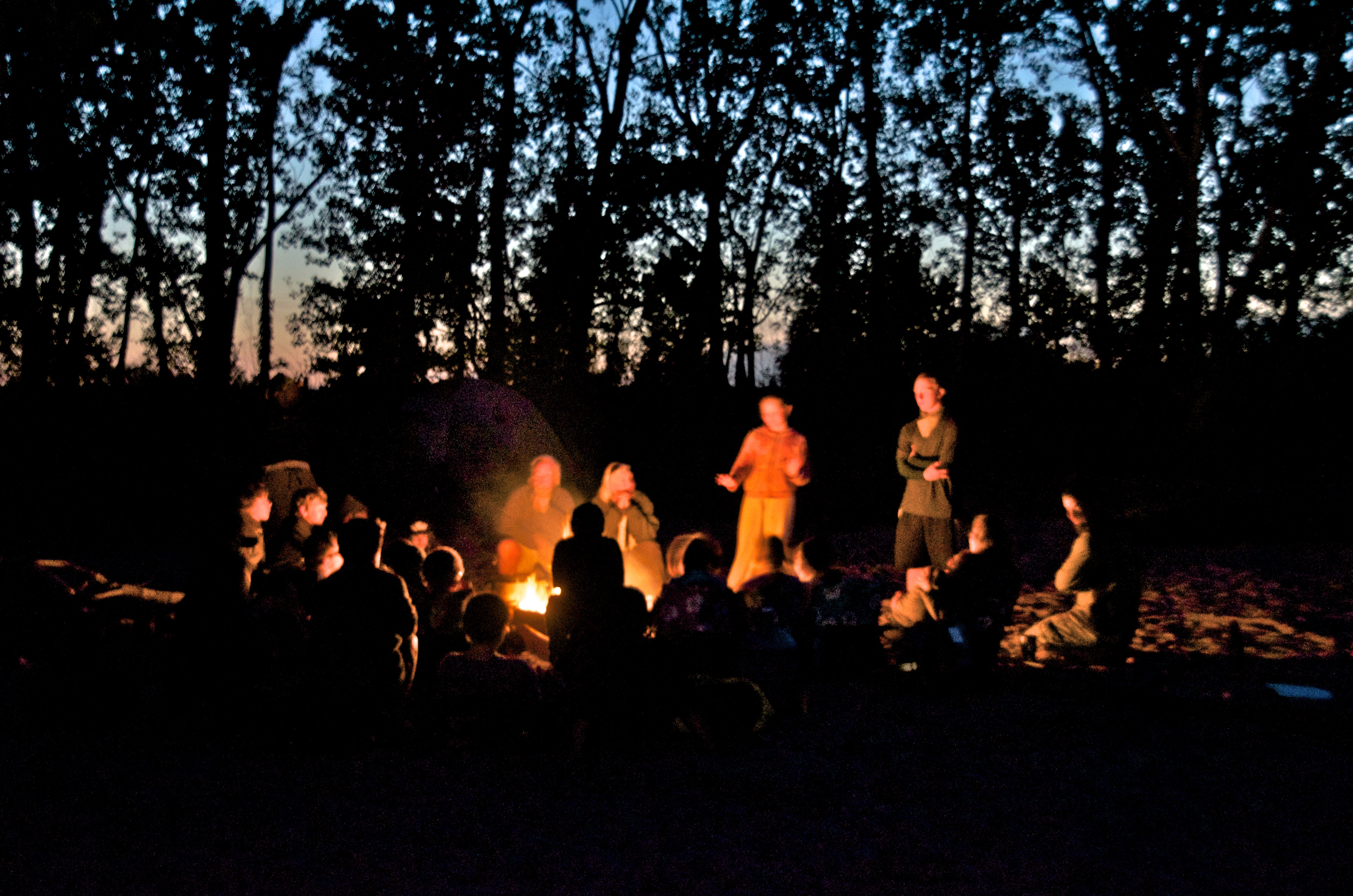 Wilderness at the doorstep. People surround a campfire at night. Image courtesy of John Ruskey.