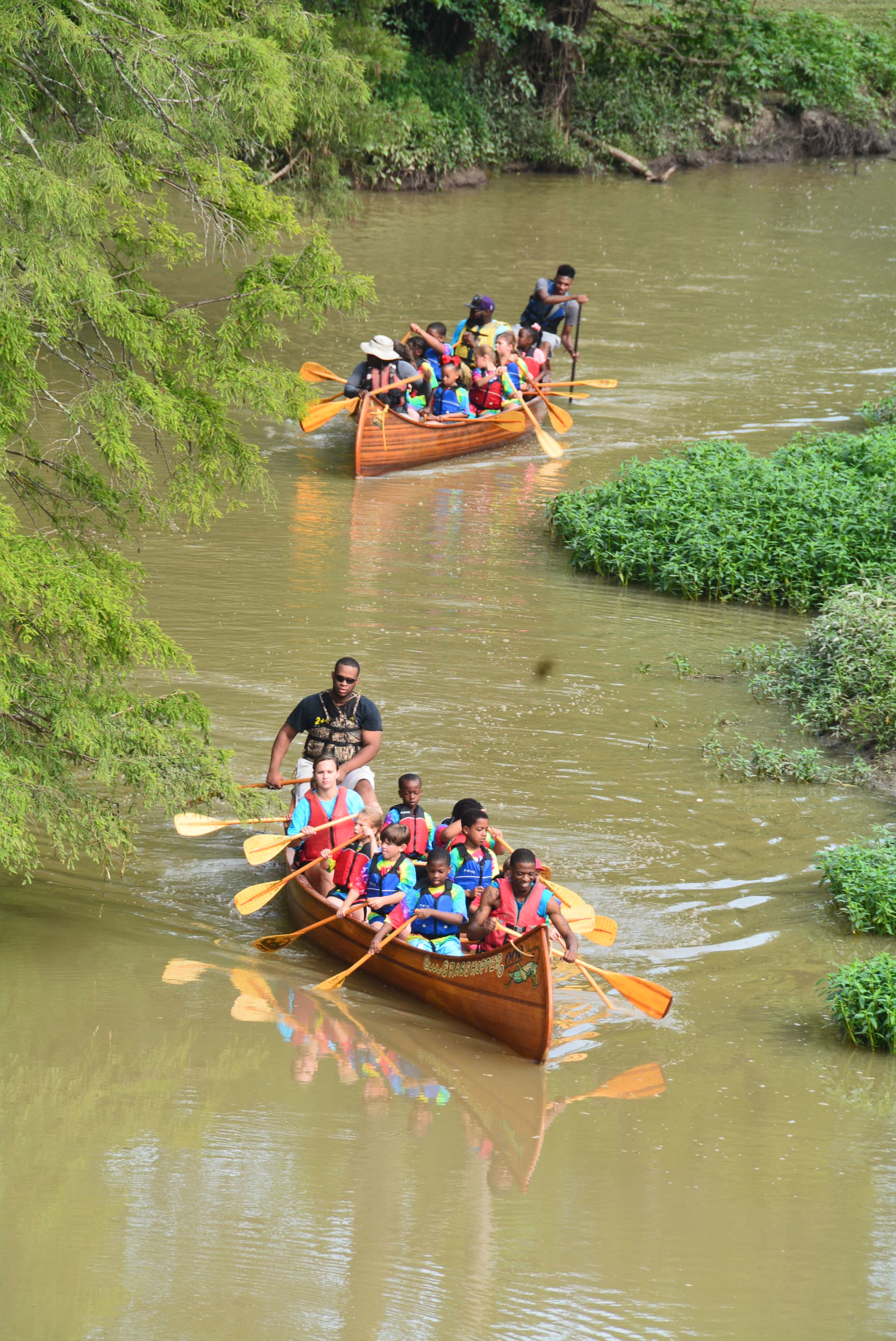 The long landscape of the river. Many young children on two different canoes are being guided through the river. Image courtesy of John Ruskey.