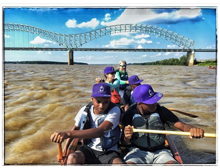 Reconnecting to the river. A guide is on a canoe with children who are all wearing purple hats. Image courtesy of Mike Brown.