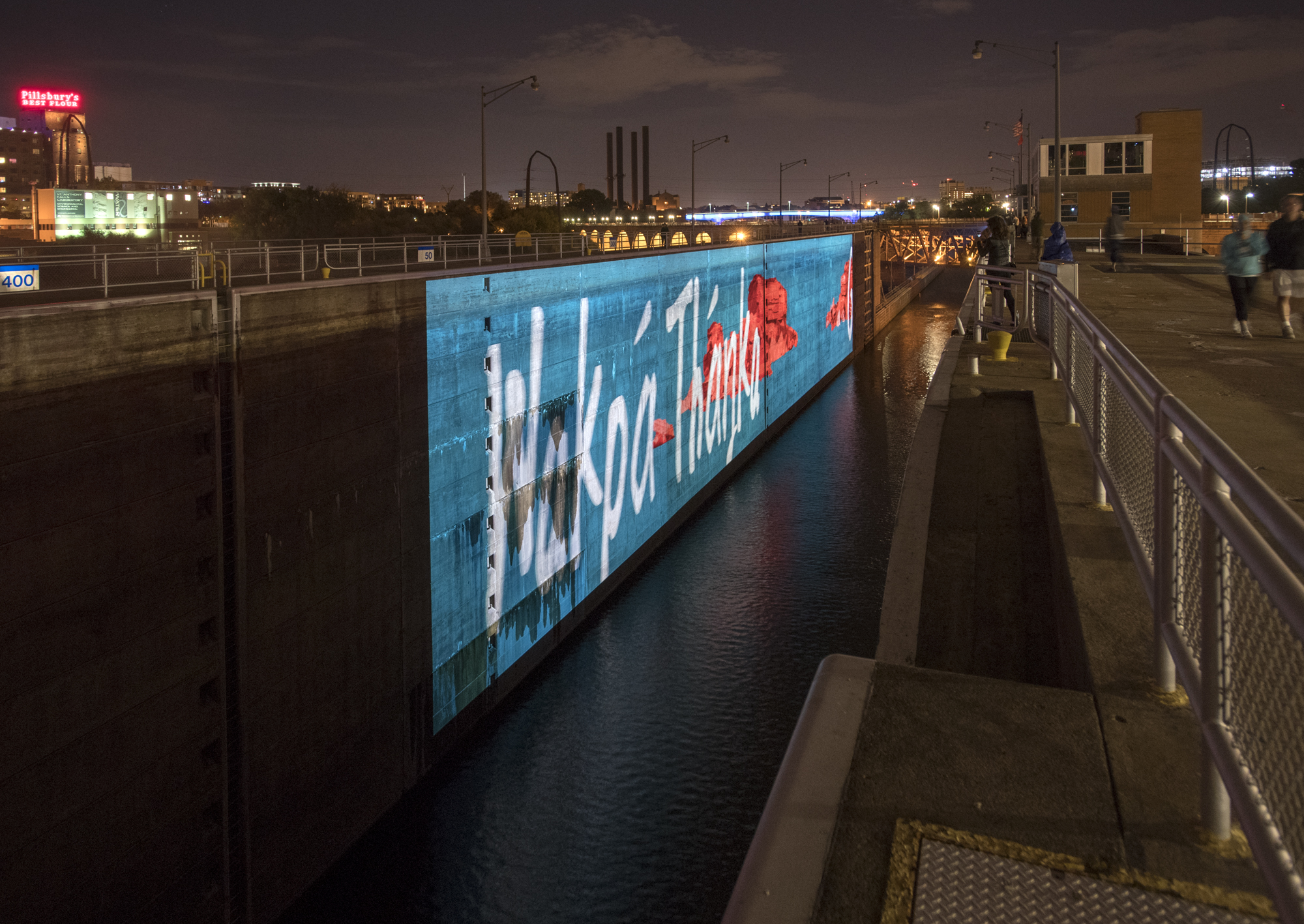Installation images of the video 'The Uncompromising Hand' (2017) by Andrea Carlson. The words 'WAKPÁ THÁŊKA' appear over a mural showing where Spirit Island used to be. Photo: Rik Sferra.
