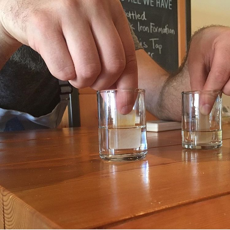A man uses pH strips on two small glasses of water.