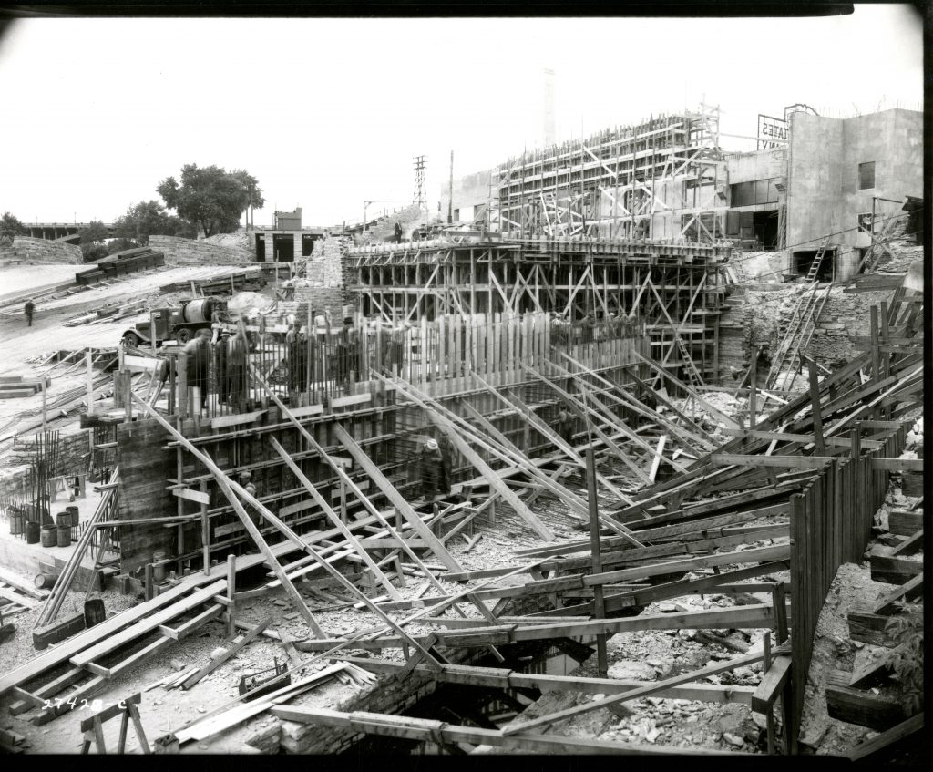 Construction photo of SAFL in 1937, showing extensive timber framing and the outflow channel, used to send water back to the river after its use in the laboratory. Viewed from near the river's edge.