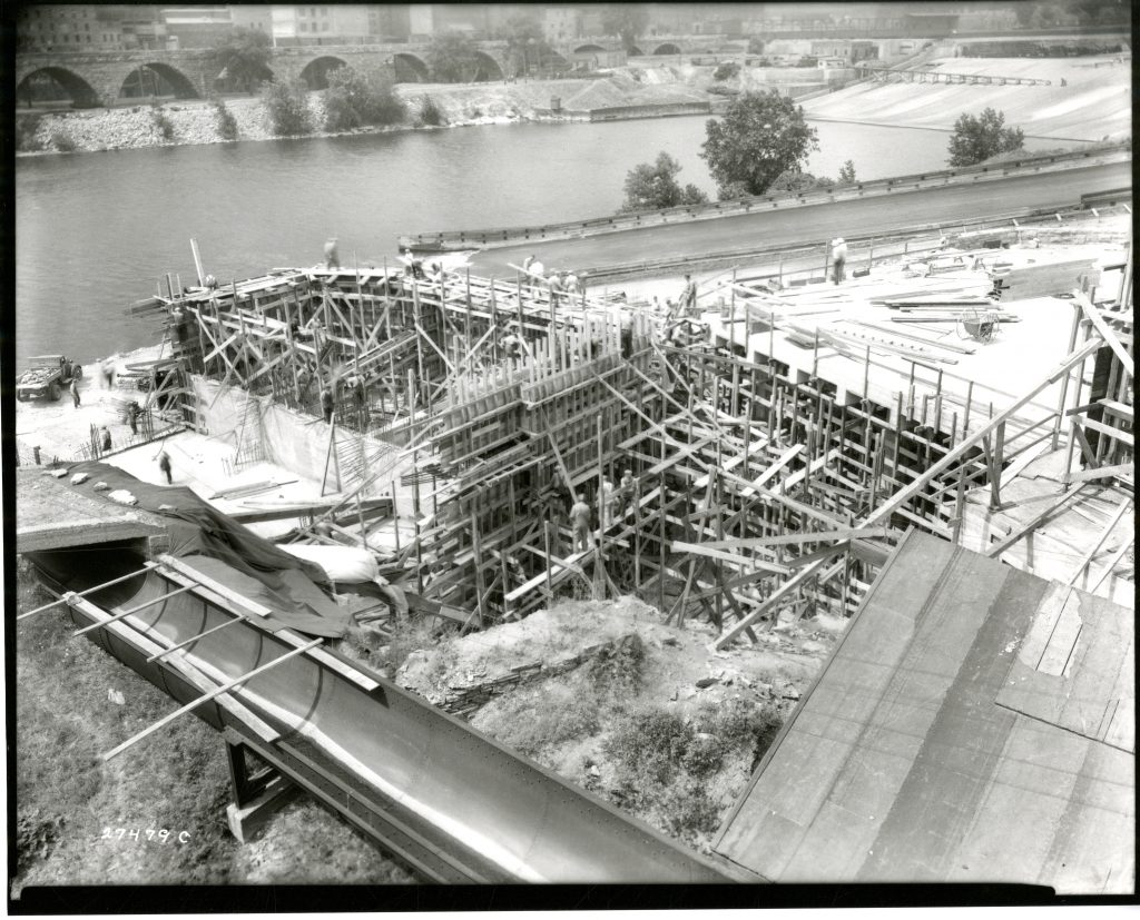 Construction of SAFL's volumetric tanks used for deep water research, the basement level used for experiments, and lower deck. The basement level was designed to flood when the river levels rose above a certain level. Notice the Stone Arch Bridge and St. Anthony Falls in the background.