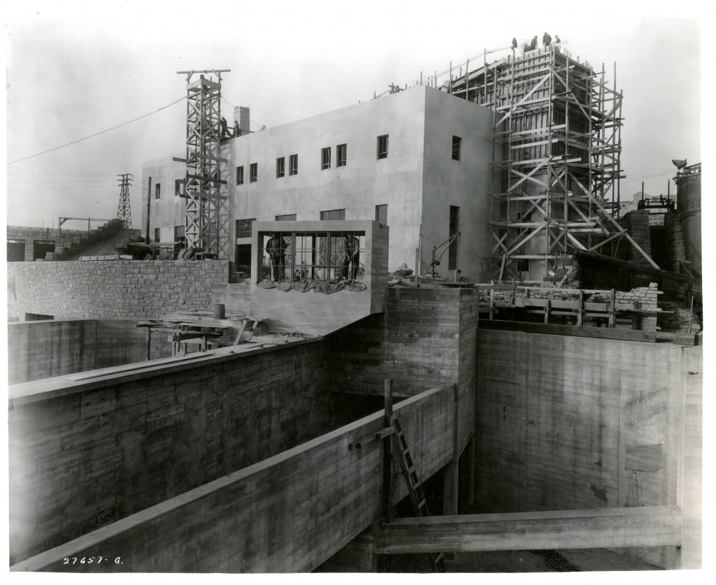 Continued construction of the laboratory in 1937. The building is starting to take shape. The volumetric tanks in the foreground are partially complete, later to be used for research requiring greater water depths.