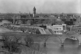 St. Anthony Falls Laboratory on the Minneapolis riverfront in 1942. The landmarks of Minneapolis are evident, as well as SAFL's intimate relationship with the river. Courtesy of University of Minnesota Archives.