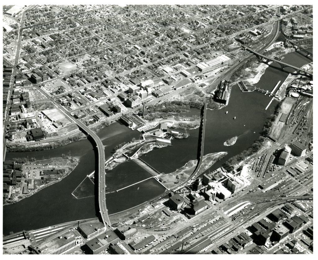 Aerial view of the Minneapolis waterfront in 1942. Notice SAFL at the upper center of the riverfront, downstream of the horseshoe dam and upstream of the Stone Arch Bridge. You can also see the Pillsbury A Mill on the upper bank.
