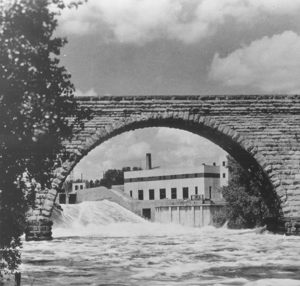 SAFL under the Stone Arch Bridge from the river itself in the 1940s. This iconic picture is beloved and has been used extensively by SAFL in publications and materials since.