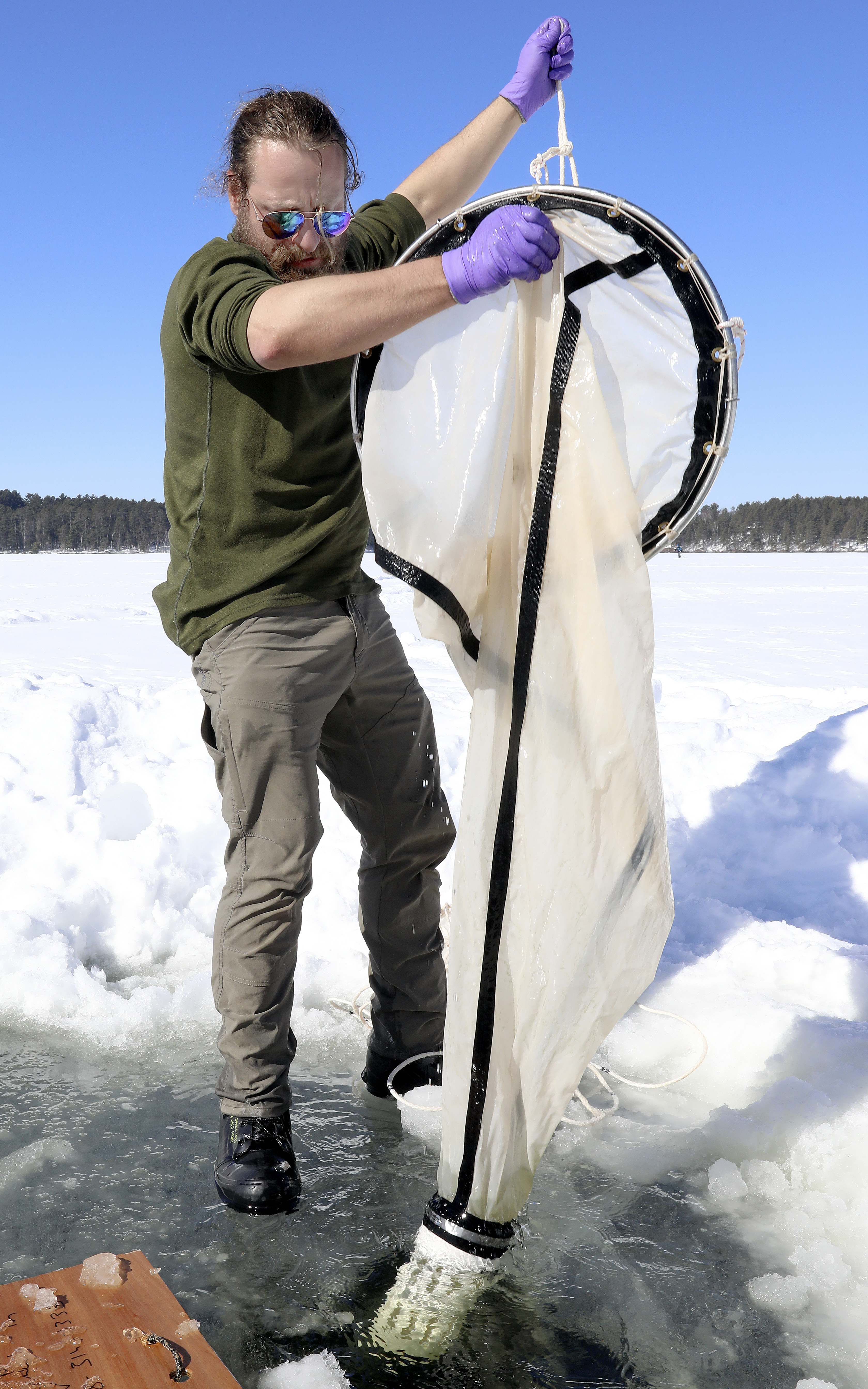 Figure 6. Scientists are discovering that lakes do not rest in the winter. Here, LLO faculty member Ted Ozersky is using a net to sample winter populations of zooplankton, small crustaceans (related to shrimp) that consume algae and in turn are consumed by fish.