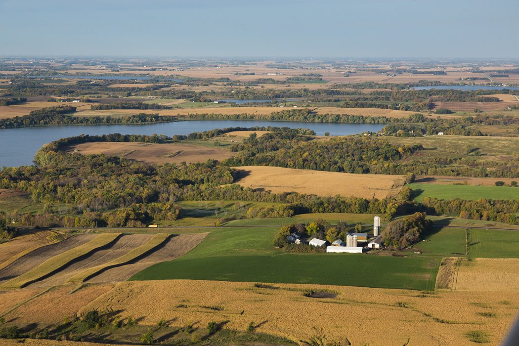 An aerial shot of a farm. The farmhouse appears in the center, and the crops surround it and are bordered by a lake.
