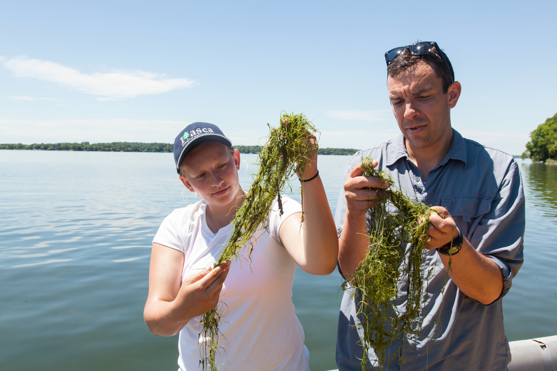 Researcher Dan Larkin and graduate student Carli Wagner look at starry stonewort on Lake Koronis.